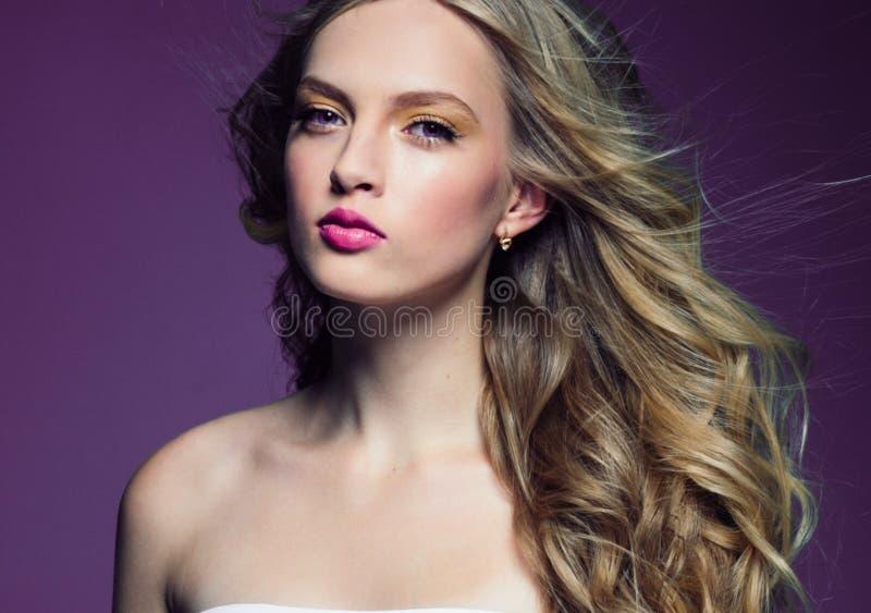 Schönes blondes Mädchen mit dem langen gelockten Haar über purpurrotem backgroun lizenzfreies stockbild