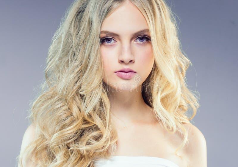 Schönes blondes Mädchen mit dem langen gelockten Haar über purpurrotem backgroun lizenzfreie stockfotografie