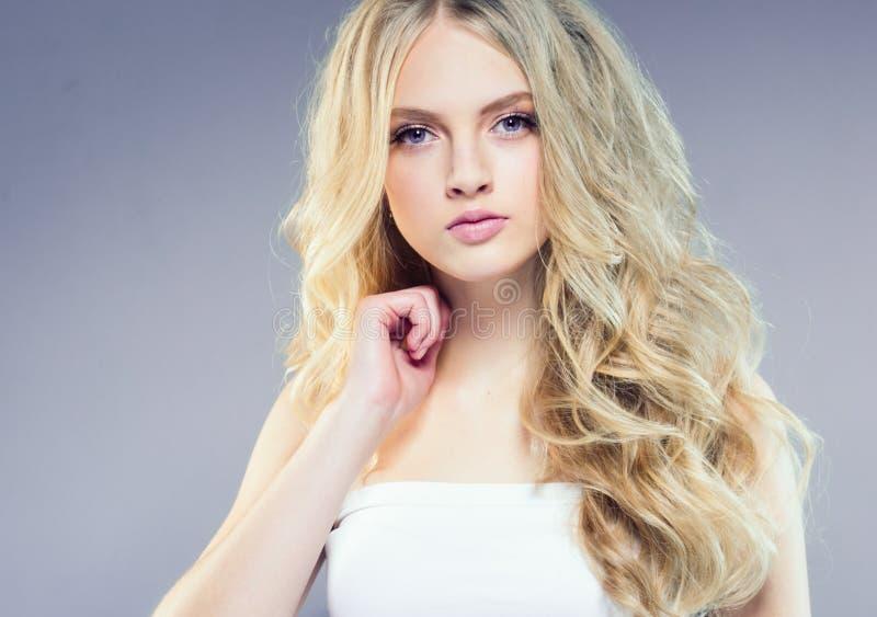 Schönes blondes Mädchen mit dem langen gelockten Haar über purpurrotem backgroun lizenzfreie stockbilder