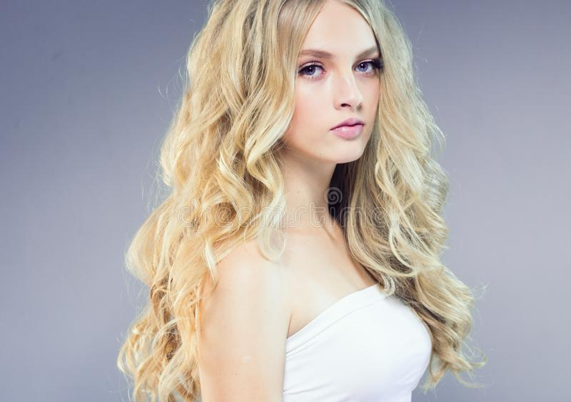 Schönes blondes Mädchen mit dem langen gelockten Haar über purpurrotem backgroun lizenzfreies stockfoto