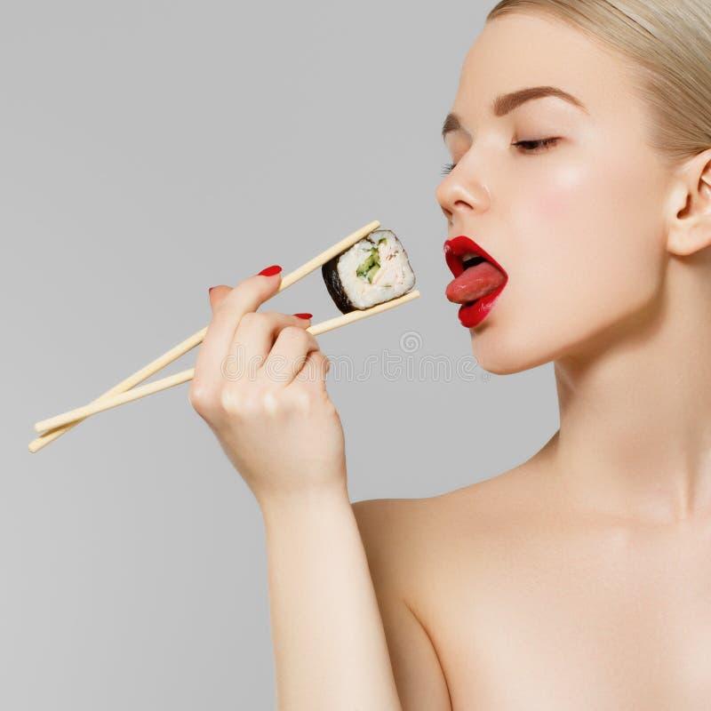 Schönes blondes Mädchen mit den roten Lippen und den manikürten Nägeln Sushi, gesunde japanische Nahrung essend Schönheitsholding stockbild