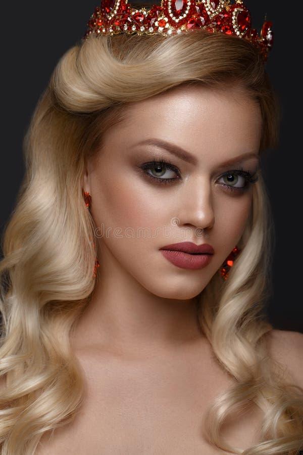 Schönes blondes Mädchen mit einer goldenen Krone, Ohrringe und Berufsabend richten her Schönes lächelndes Mädchen lizenzfreies stockbild