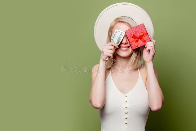 Schönes blondes Mädchen mit Geld und Geschenkbox stockfotos