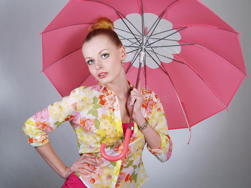 Schönes blondes Mädchen mit rosafarbenem Regenschirm stockfotos