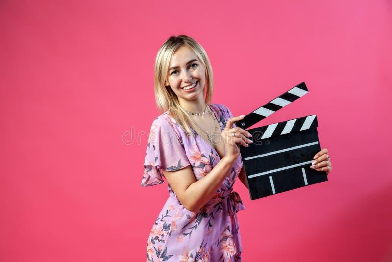 Schönes blondes Mädchen in purpurrote sundress hält einen offenen clapperboard Filmemacher im Schwarzen mit weißen Streifen, um a stockbilder