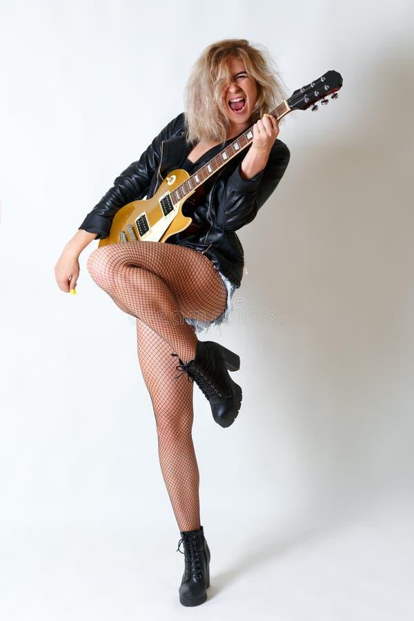 Schönes blondes Mädchen spielt emotional Gitarre Weißer Hintergrund lizenzfreies stockbild