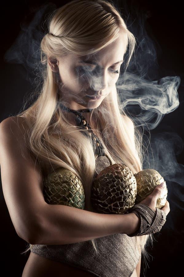 Schönes blondes mit drei Dracheeiern stockfoto