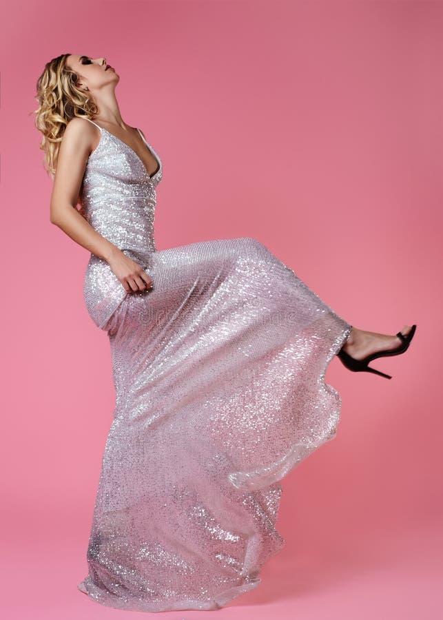 Schönes blondes in Mode Kleid Sexy Frau, die auf rosa Hintergrund in der Luxusglanz-Kleidung, Schuhe aufwirft Zauber-Tritt lizenzfreie stockfotos