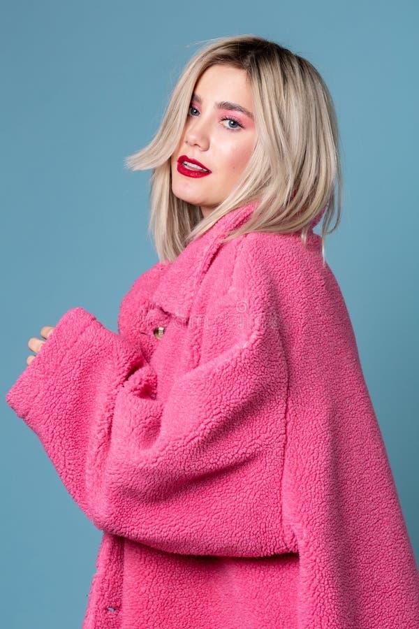Schönes blondes Mode-Modell, das verlockend im rosa Mantel aufwirft lizenzfreie stockbilder