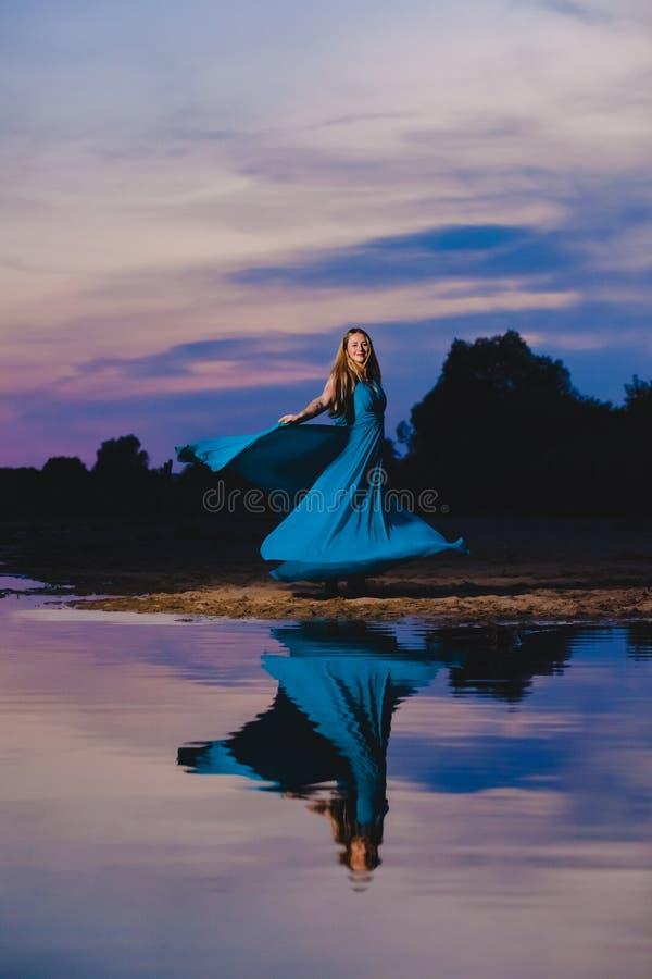 Schönes blondes Modell im Kleid der blauen Luft, das gerade nahe dem Seerand aufwirft lizenzfreie stockbilder