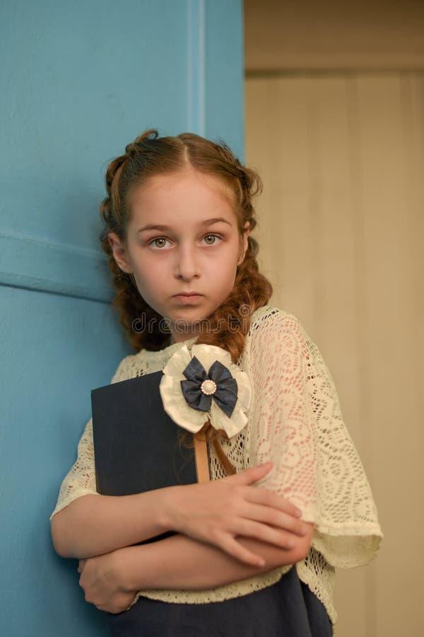 Schönes blondes Schulmädchen mit Notizbüchern in der Schule stockfotografie