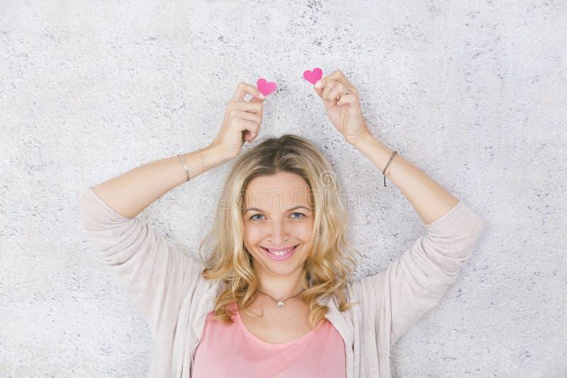 Schönes, blondes und sexy Mädchen wirft mit zwei Rosa, Papierherzen vor grauem, konkretem Hintergrund auf lizenzfreie stockfotos