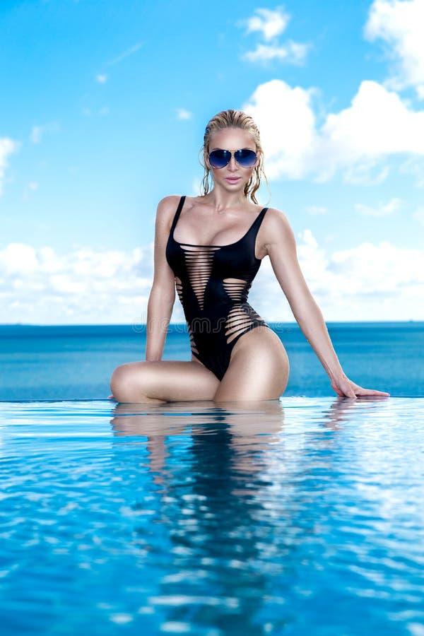 Schönes Blondinemodell mit dem nassen Haar und eleganten dem Make-up, die in einem Pool sitzt stockbild