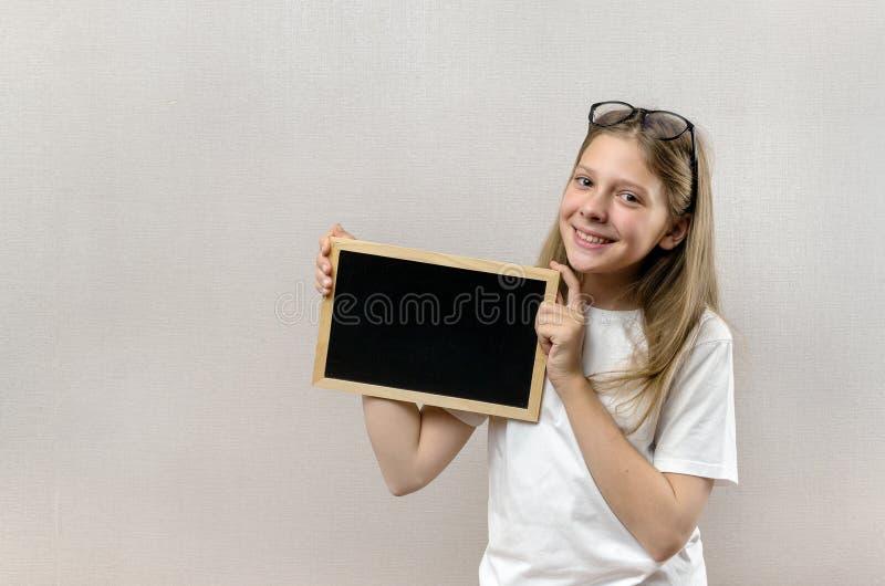 Sch?nes boshaftes M?dchen mit den Gl?sern, die herein ein Zeichen ihre H?nde halten Kopie-Raum stockbild