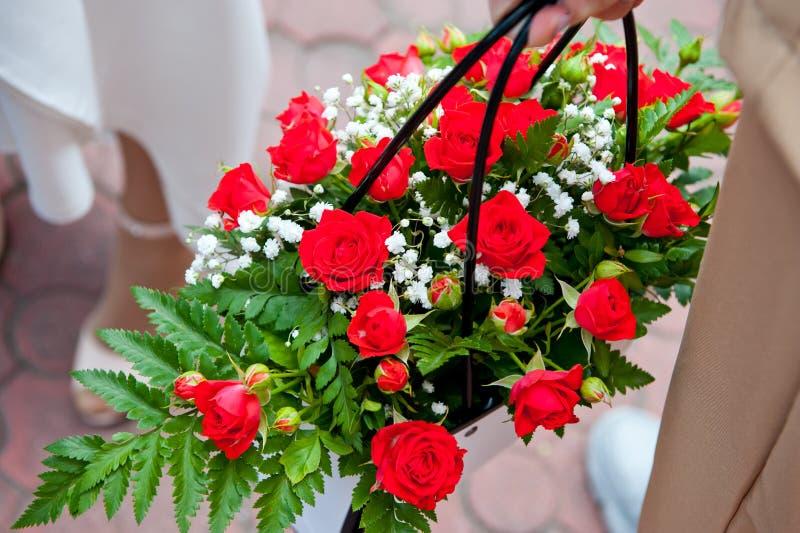 Schönes Bouquet mit roten Rosen in einem Korbkorb stockfotos