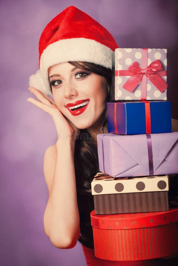 Schönes Brünettemädchen im Weihnachtshut mit Geschenken lizenzfreie stockfotografie