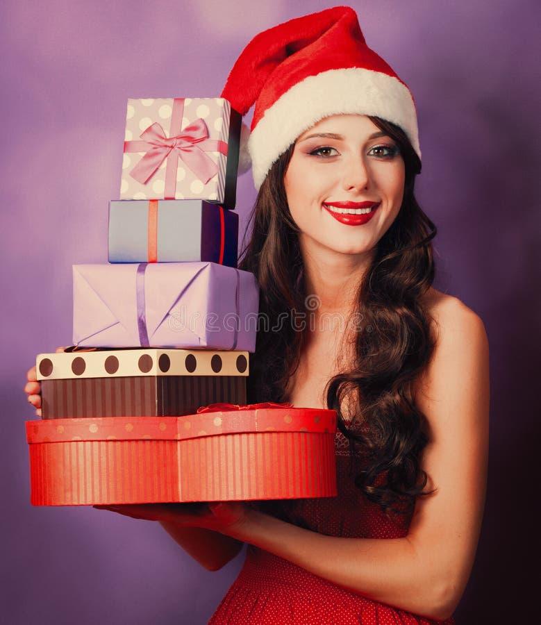 Schönes Brünettemädchen im Weihnachtshut mit Geschenken stockfotos
