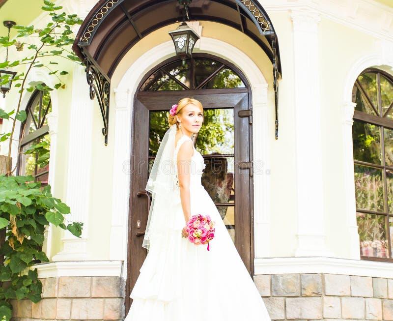 Schönes Brautmädchen im Hochzeitskleid mit Blumenstrauß von Blumen, draußen Porträt lizenzfreie stockfotos