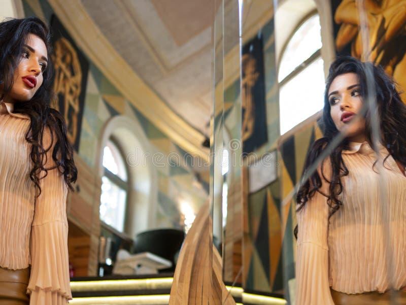 Schönes brunette-haariges vorbildliches Mädchen schaut in einem großen Spiegel Art und Weisebaumusteraufstellung stockbilder