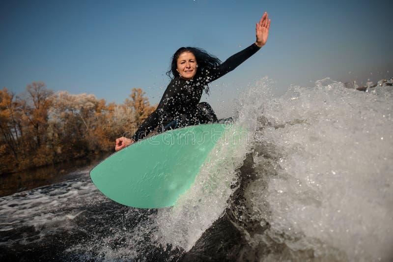 Schönes brunette Mädchen, das auf das grüne wakeboard auf den verbiegenden Knien springt stockbild