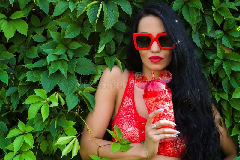 Schönes brunette Mädchen in den roten Gläsern mit Flasche Wasser stockbilder