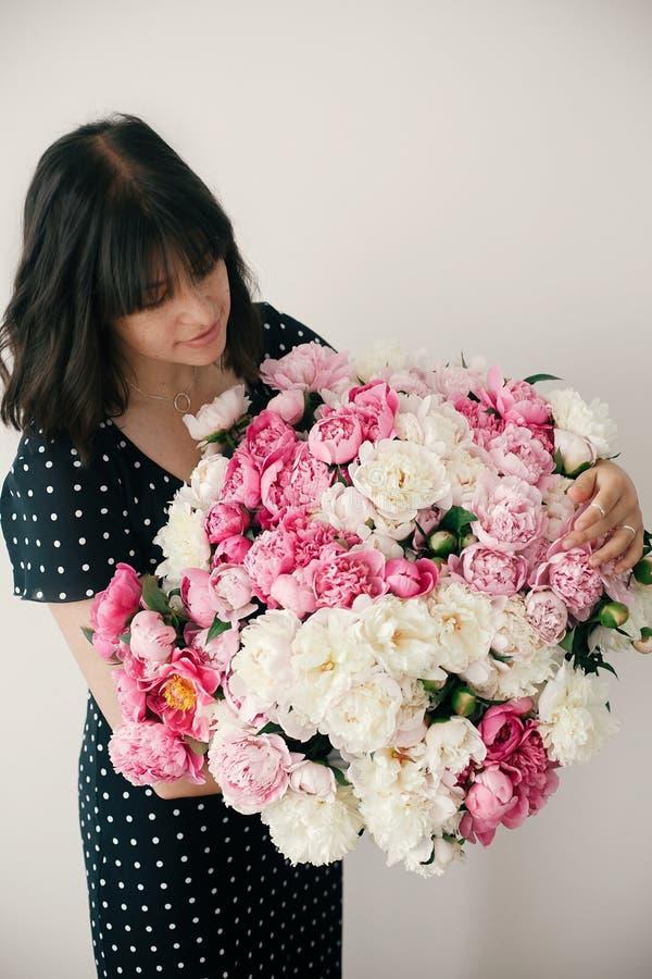 Schönes brunette Mädchen im Weinlesekleid, das großen Blumenstrauß mit den Rosa- und weißenpfingstrosen hält Glückliche stilvolle stockfoto