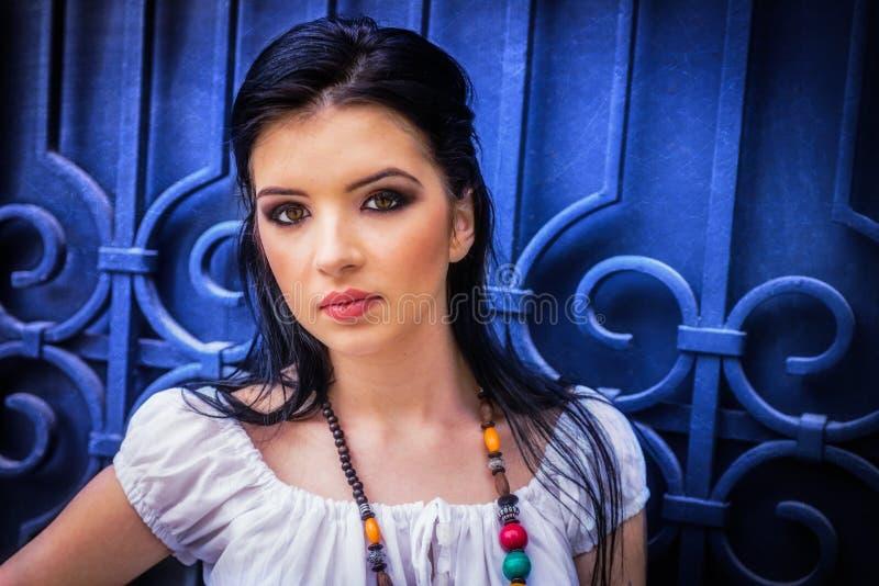 Schönes brunette Mädchen mit dem großen Augen- und weißemkleid, s schauend stockbilder