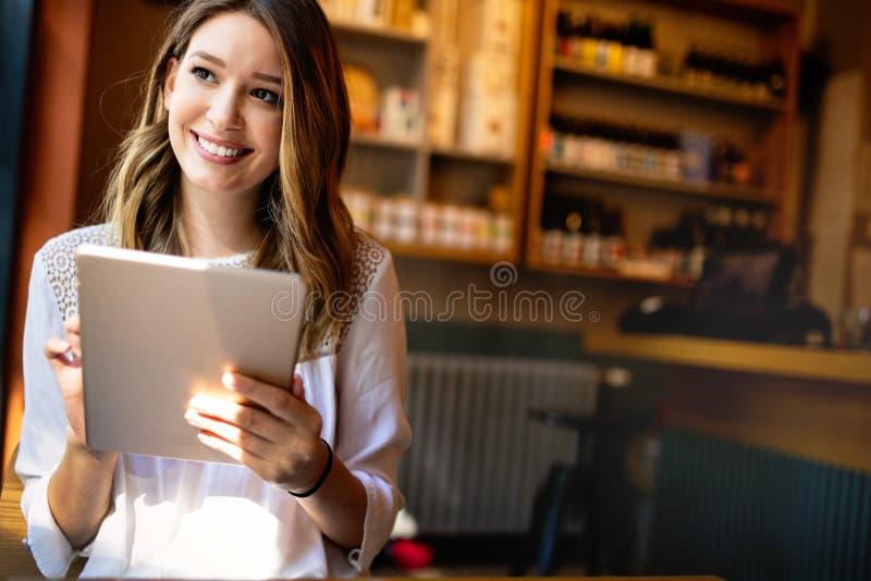Schönes brunette Mädchen unter Verwendung des Laptops für Arbeit, freiberuflich tätig, bloggend und studieren und kaufen stockbild
