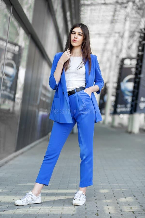 Schönes brunette Modell, das in der blauen Kleidung aufwirft Das Konzept der Mode, der Schönheit, des Einkaufens und des Lebensst stockfotos