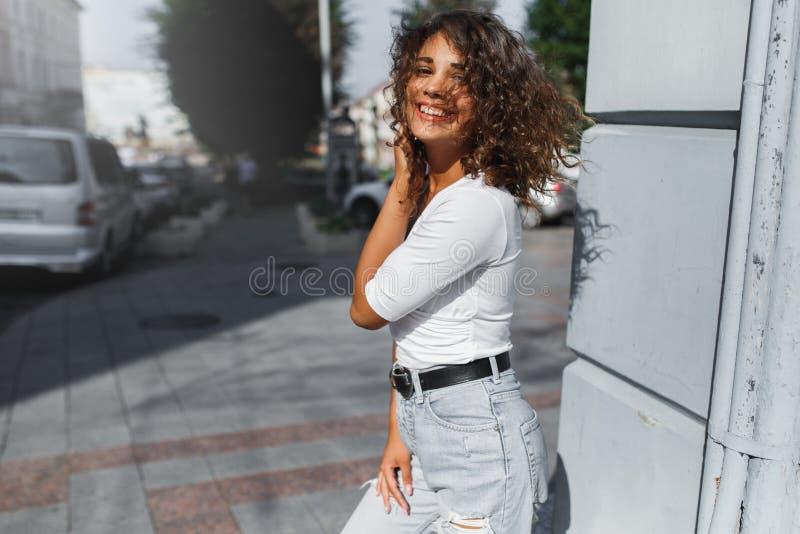 Schönes brunette sexy Mädchen, das in die Stadt mit langem Fliegen des gelockten Haares auf dem Wind geht lizenzfreie stockfotos