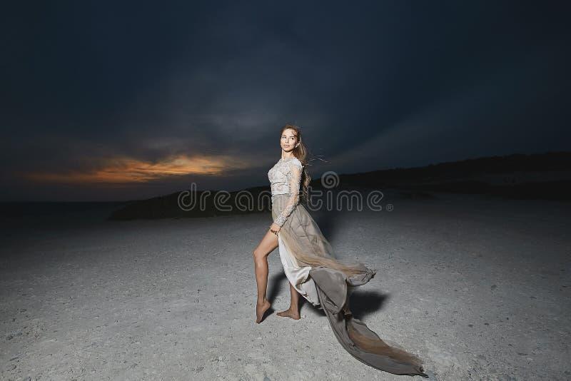 Schönes brunette vorbildliches Mädchen mit den langen sexy Beinen im modernen Spitzekleid, das an der Seeküste bei dem Sonnenunte stockfotografie