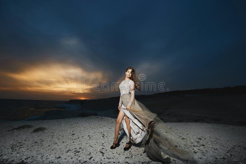 Schönes brunette vorbildliches Mädchen mit den langen sexy Beinen im modernen Spitzekleid, das an der Seeküste bei dem Sonnenunte lizenzfreie stockfotografie