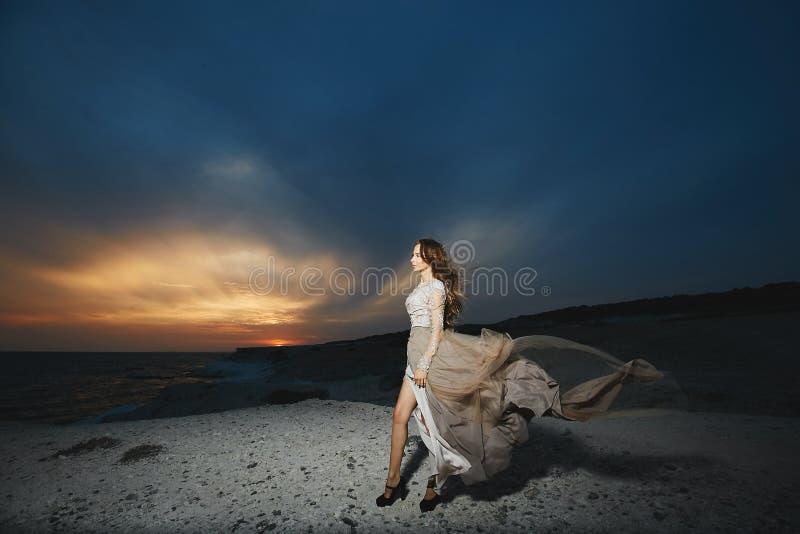 Schönes brunette vorbildliches Mädchen mit den langen sexy Beinen im modernen Spitzekleid, das an der Seeküste bei dem Sonnenunte lizenzfreie stockfotos