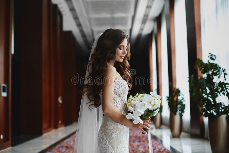 Sch?nes brunette vorbildliches M?dchen mit perfektem K?rper und mit Heiratsfrisur in einem Heiratsspitzekleid mit einem Blumenstr lizenzfreie stockbilder