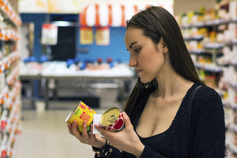 Schönes Brunettefraueneinkaufen im Supermarkt Wählen von NichtGMO-Lebensmittel lizenzfreie stockfotos