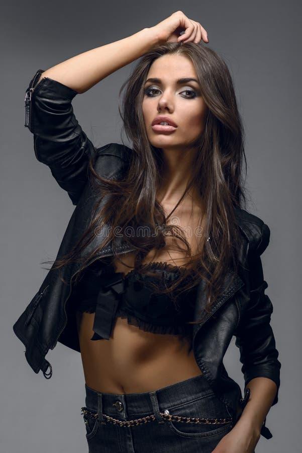 Schönes Brunettefrauenmode-modell, das am Studio über die Wand aufwirft stockfotografie