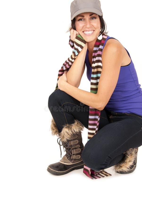 Schönes Brunettelächeln geduckt unten auf den Knien, die Stiefel tragen lizenzfreie stockbilder