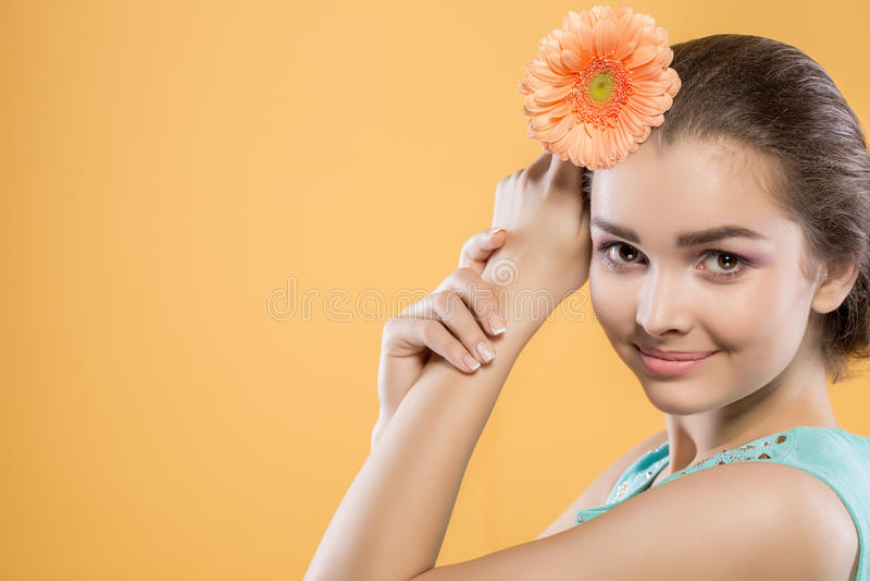 Schönes Brunettemädchen auf einem gelben Hintergrund Frau hält Gerberablume nahe dem Kopf Nahaufnahme lizenzfreies stockfoto
