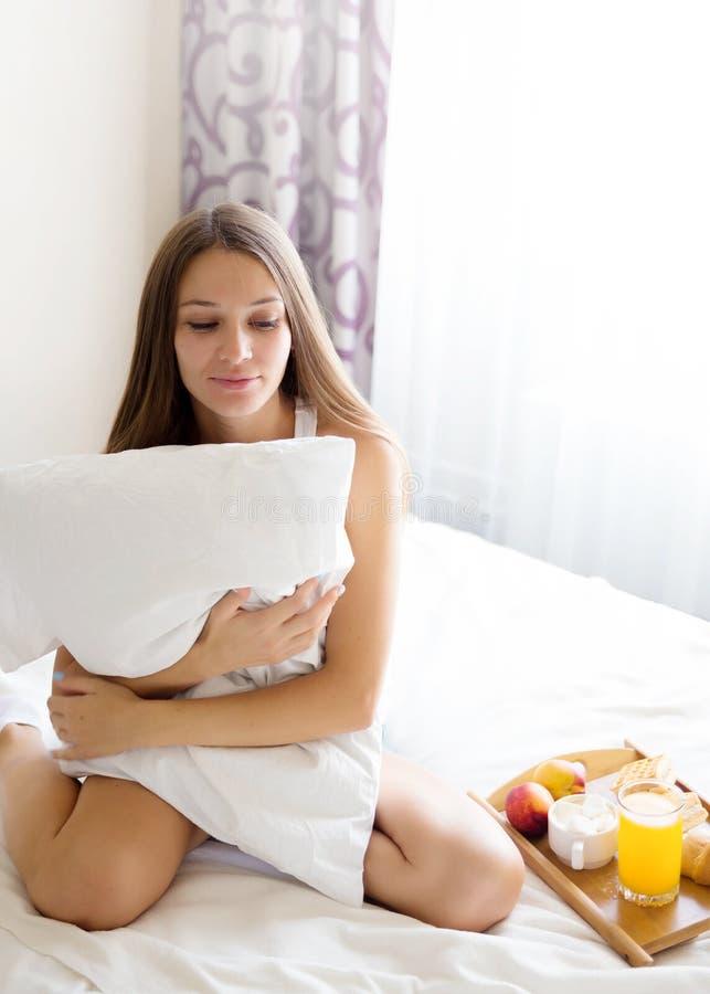 Schönes Brunettemädchen, das ein gesundes Frühstück im Bett isst stockfotos