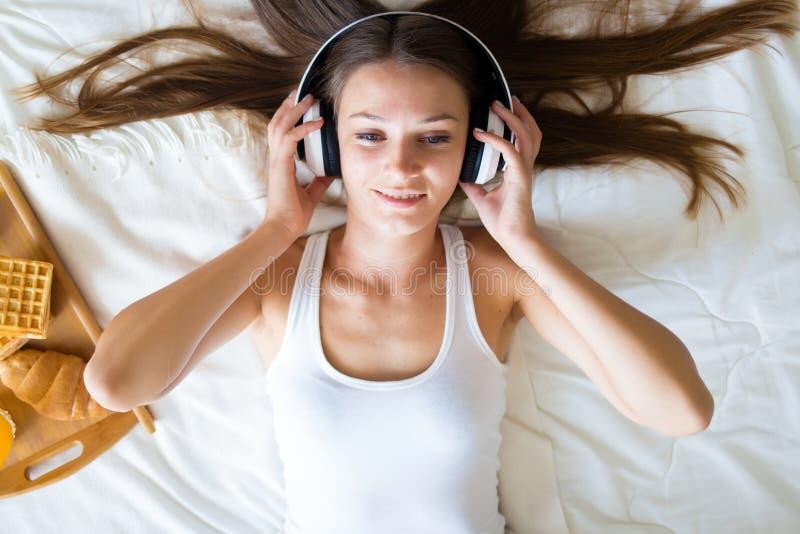 Schönes Brunettemädchen, das Musik auf Kopfhörern im Bett hört Frühstücks-Frau morgens stockfotografie