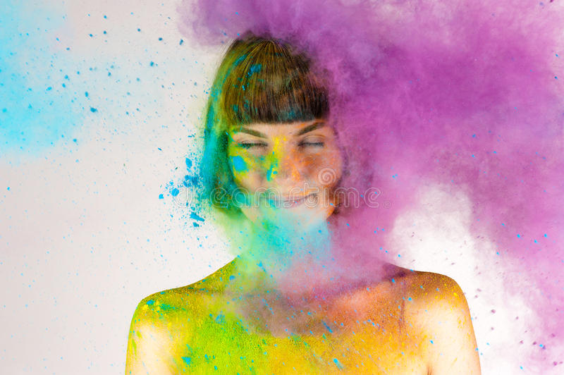 Schönes Brunettemädchen in den Farben Holi auf einem Weiß lizenzfreie stockfotos