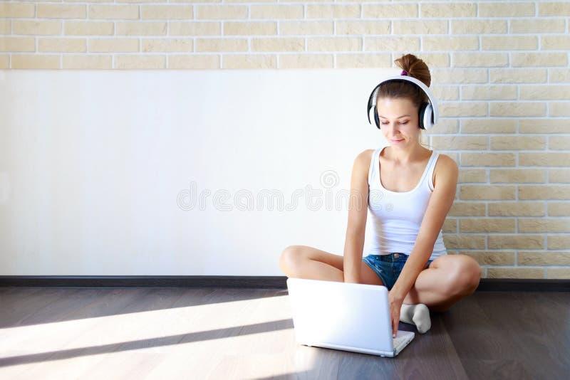 Schönes Brunettemädchen in den Kopfhörern hörend Musik auf Laptop Kopienraum stockbilder