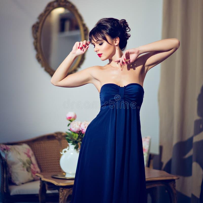 Schönes Brunettemädchen in einem blauen Kleid, das im Innenraum steht stockbild