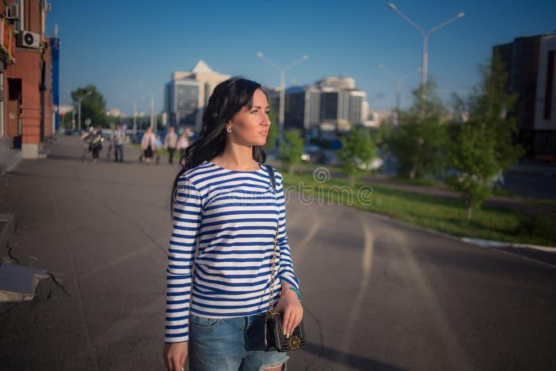 Schönes Brunettemädchen geht durch die Stadt lizenzfreies stockfoto