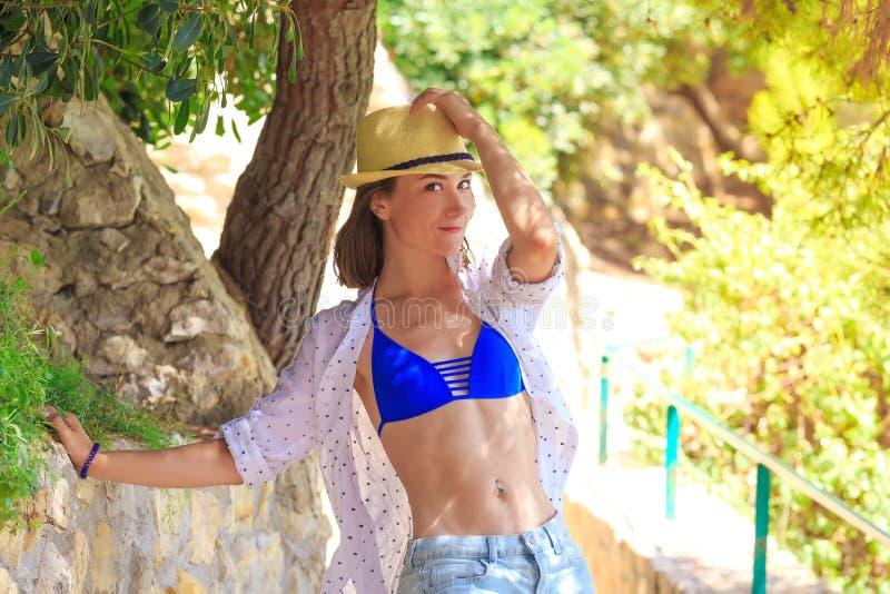 Schönes Brunettemädchen im Bikini, der im Baumschatten steht Frauentourist auf Sommerurlaubsort lizenzfreie stockbilder