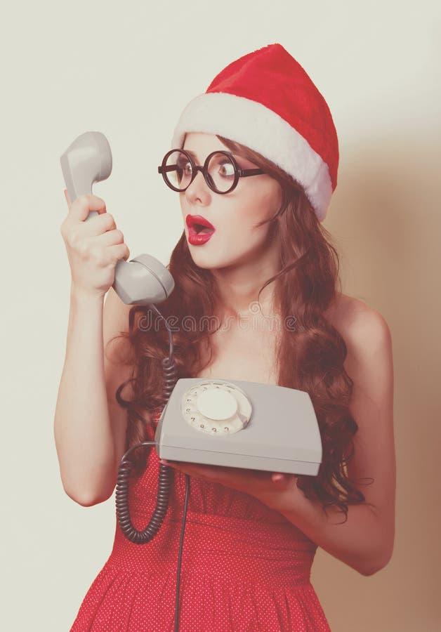 Schönes Brunettemädchen im Weihnachtshut mit Telefon auf yello lizenzfreie stockfotografie