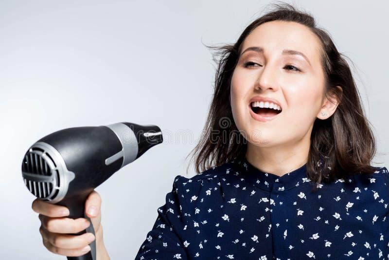 Schönes Brunettemädchen mit Augen schloss das Schreien, in ein Isolat Hairdryer die blauen Hemdglückgefühle an Hand singend lizenzfreie stockbilder