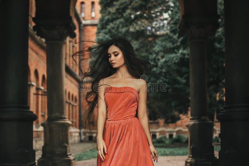 Schönes Brunettemädchen, mit dem sehr langen Haar, in einer Orange, Weinlesekleid stockfoto