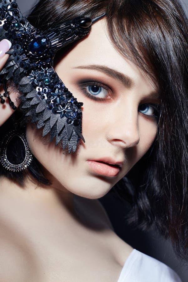 Schönes Brunettemädchen mit den großen blauen Augen, die eine schwarze Broschendekoration in Form von Vögeln halten Natürliches M stockfotos