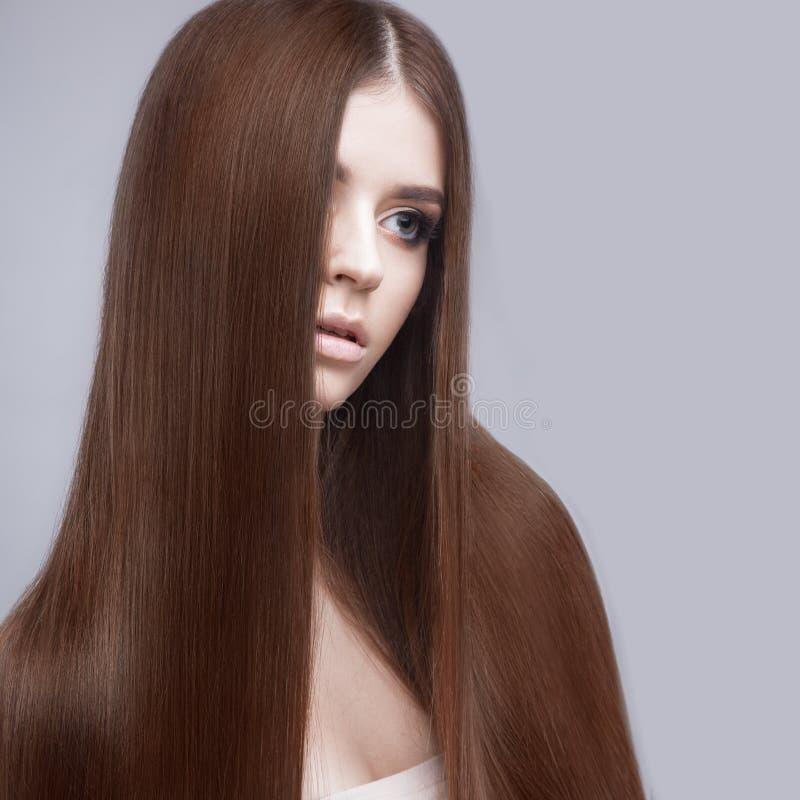 Schönes Brunettemädchen mit einem tadellos glatten Haar und einem klassischen Make-up Schönes lächelndes Mädchen lizenzfreie stockfotos